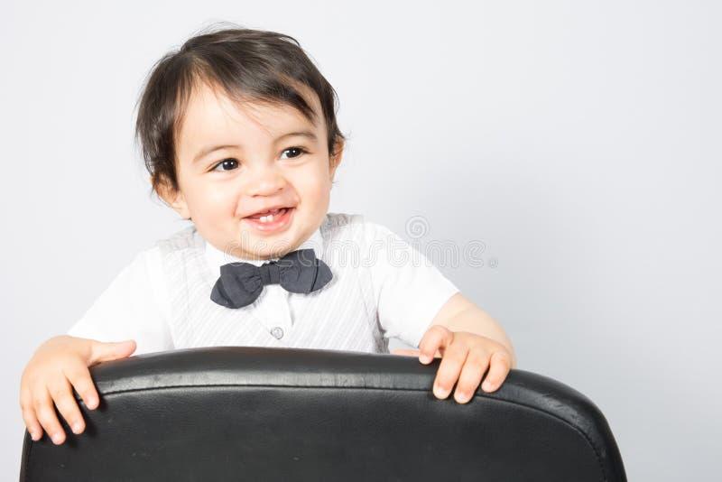 Gelukkige blij mooi weinig jongen op witte achtergrond die zich op stoel bevinden royalty-vrije stock afbeelding