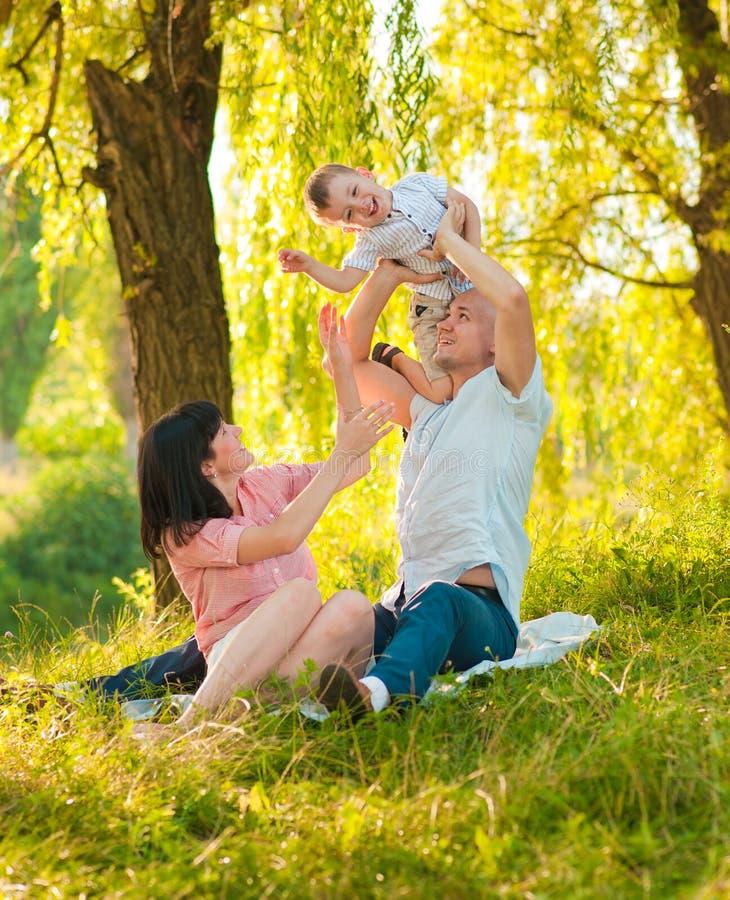 Gelukkige blije jonge familie met kind stock afbeelding