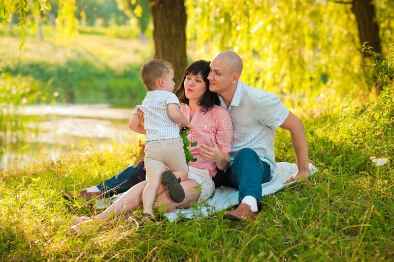 Gelukkige blije jonge familie met kind in openlucht stock fotografie