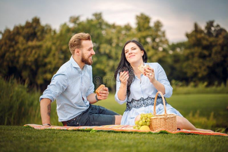 Gelukkige blije jonge familieechtgenoot en zijn zwangere vrouw die pret hebben samen in openlucht, bij picknick in de zomerpark stock foto's