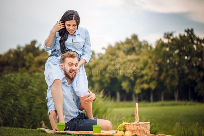 Gelukkige blije jonge familieechtgenoot en zijn zwangere vrouw die pret hebben samen in openlucht, bij picknick in de zomerpark stock fotografie