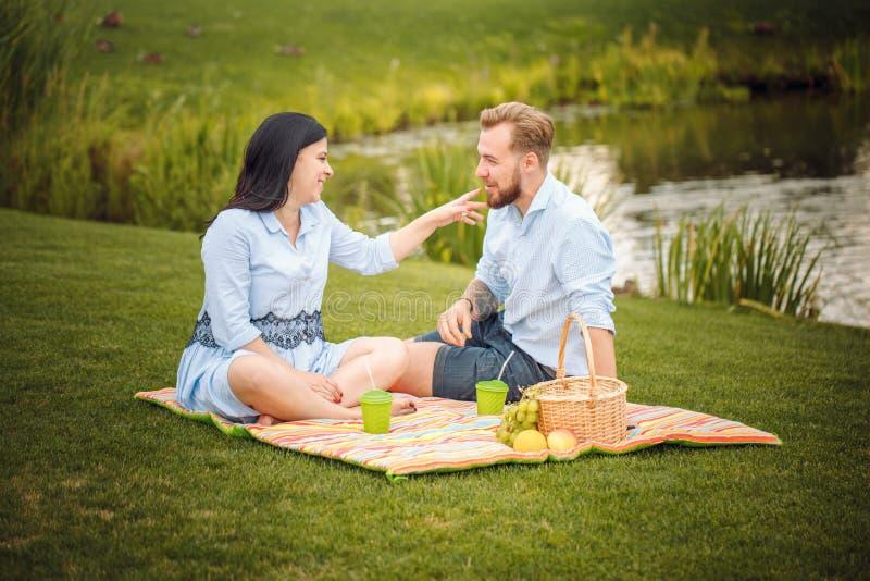 Gelukkige blije jonge familieechtgenoot en zijn zwangere vrouw die pret hebben samen in openlucht, bij picknick in de zomerpark royalty-vrije stock foto
