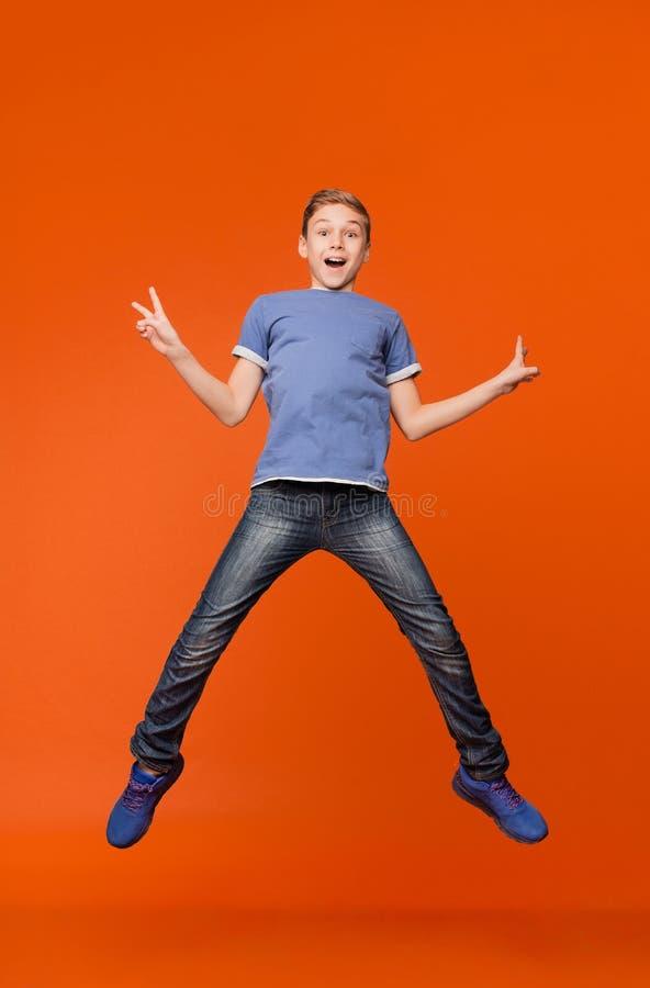 Gelukkige blije jongen die omhoog in lucht, aantonende v-tekens springt royalty-vrije stock afbeeldingen