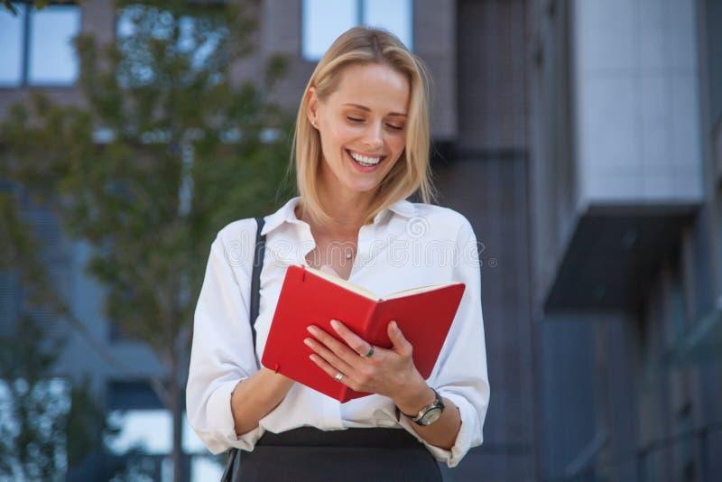Gelukkige blonde bedrijfsvrouw met notitieboekje tegen van de bureaubouw royalty-vrije stock foto's