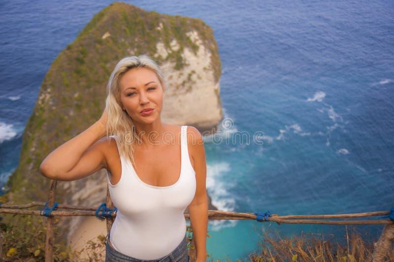 Gelukkige blonde toeristenvrouw die vrij op de overweldigende mening van mooi overzees klippenstrand bij gezichtspunt die van de  stock foto