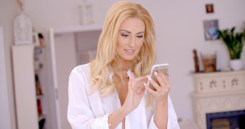 Gelukkige Blonde Vrouw die bij haar Mobiele Telefoon doorbladeren stock afbeeldingen