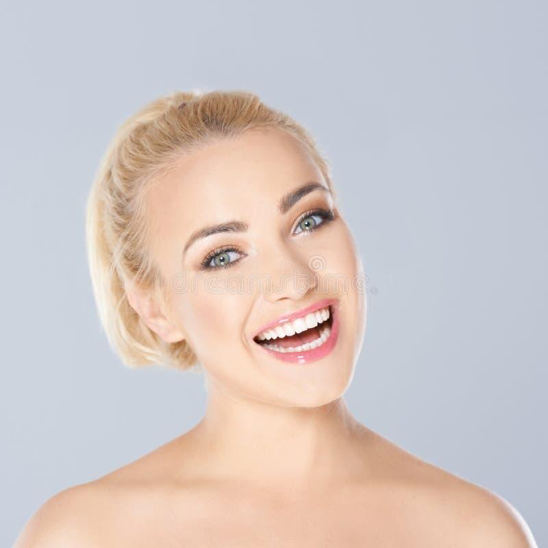 Gelukkige blonde vrouw met een richtende toothy glimlach stock foto