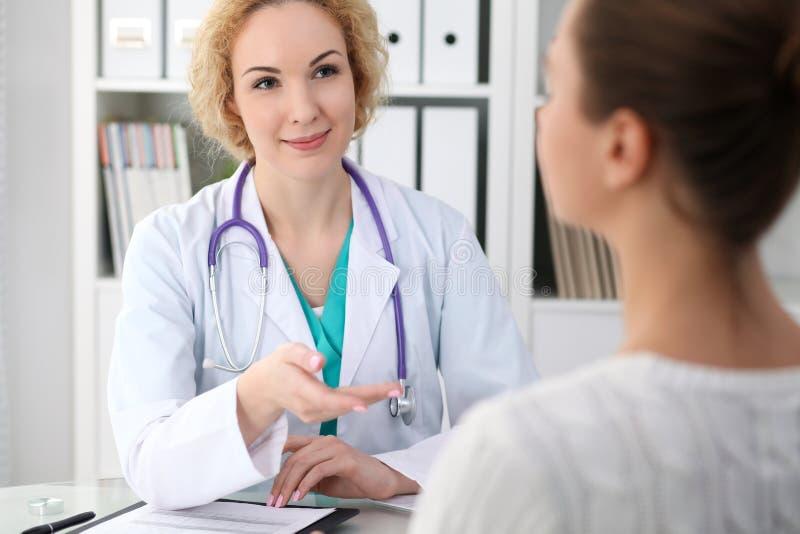 Gelukkige blonde vrouwelijke arts en patiënt die algemeen medisch onderzoekresultaten bespreken Geneeskunde, gezondheidszorg en h royalty-vrije stock afbeeldingen