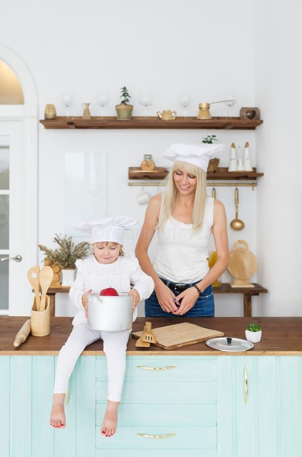 Gelukkige blondemoeder en weinig dochter in wit GLB in huiskeuken stock foto's