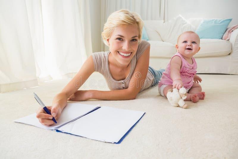 Gelukkige blondemoeder met haar babymeisje die op een voorbeeldenboek schrijven stock fotografie