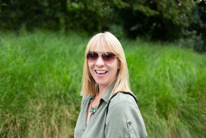 Gelukkige blondevrouw die voor een groene natuurlijke achtergrond glimlacht De zomer, in openlucht en levensstijlconcept royalty-vrije stock afbeeldingen