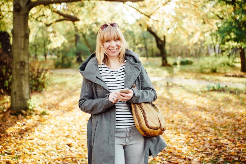 Gelukkige blondevrouw in het herfstbos of park texting met haar mobiele telefoon Mededeling, technologie en in openlucht concept royalty-vrije stock afbeeldingen