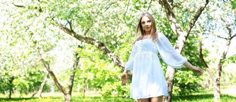 Gelukkige blondevrouw op een achtergrond van bloeiende de lentetuin met haar die handen aan de hemel wordt opgeheven royalty-vrije stock foto