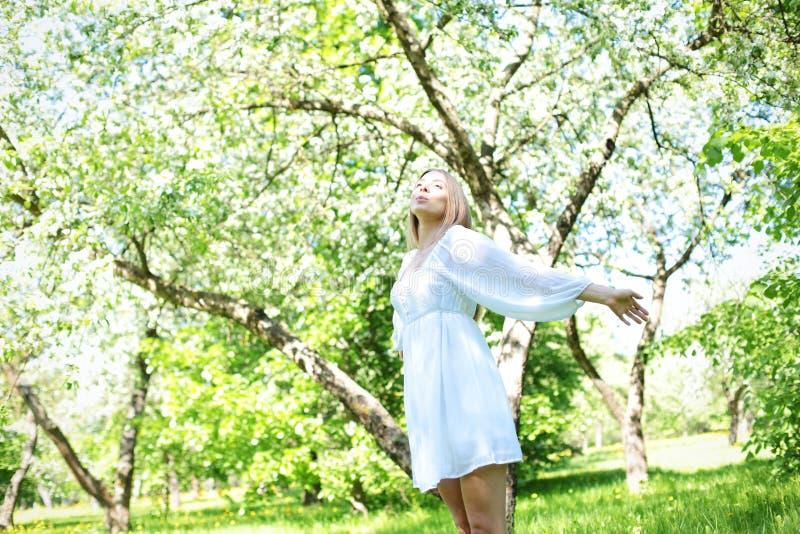 Gelukkige blondevrouw op een achtergrond van bloeiende de lentetuin met haar die handen aan de hemel wordt opgeheven royalty-vrije stock afbeeldingen