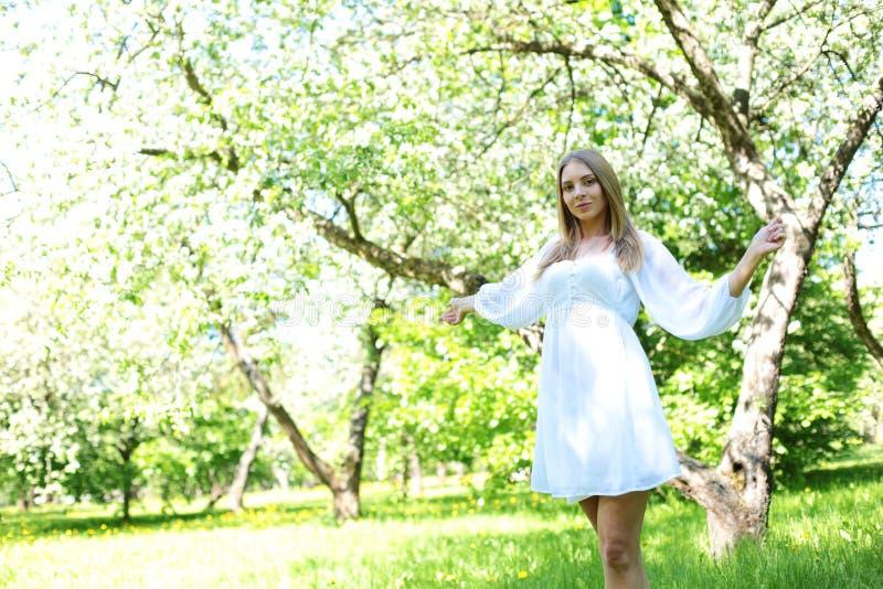 Gelukkige blondevrouw op een achtergrond van bloeiende de lentetuin met haar die handen aan de hemel wordt opgeheven royalty-vrije stock fotografie