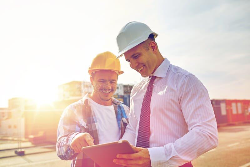 Gelukkige bouwers in bouwvakkers met tabletpc in openlucht stock foto