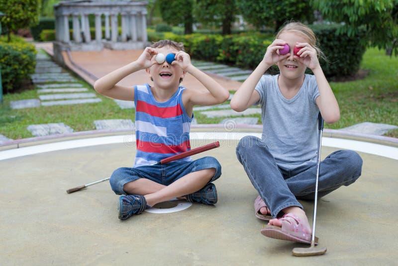 Gelukkige broer en zuster die minigolf spelen royalty-vrije stock fotografie