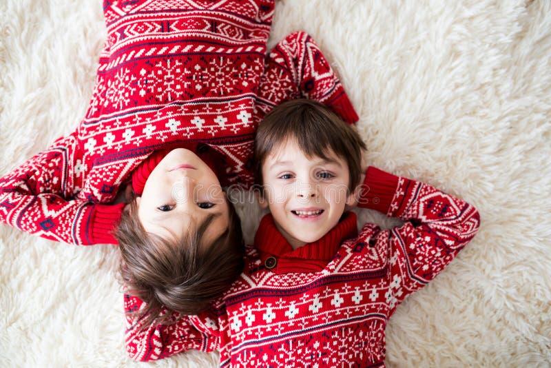 Gelukkige broers, baby en peuterkinderen, die thuis op witte deken, het glimlachen koesteren stock fotografie