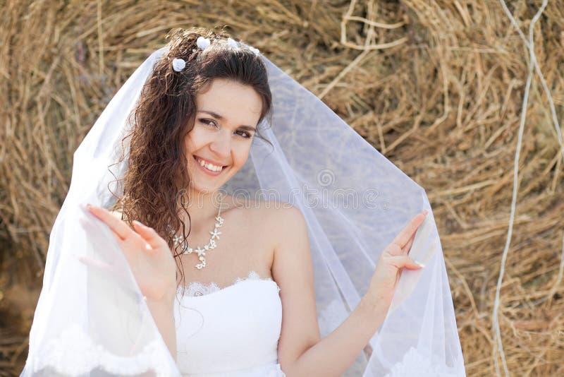 Gelukkige bruid dichtbij hooi royalty-vrije stock fotografie