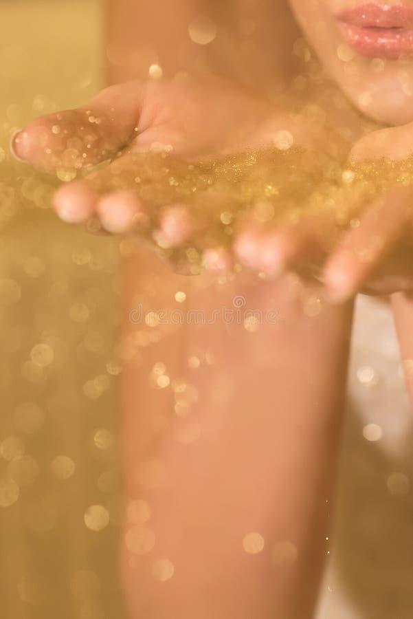 Gelukkige bruid die gouden klatergoud van haar handen wegblazen royalty-vrije stock fotografie