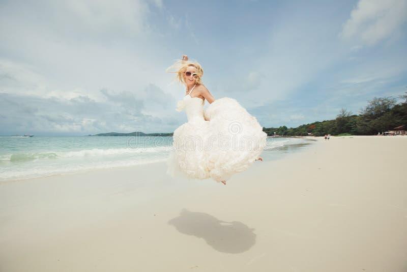 Gelukkige bruid die in huwelijkskleding bij het overzees springen jonge gelukkige vrouw op strand stock foto's