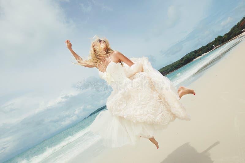 Gelukkige bruid die in huwelijkskleding bij het overzees springen jonge gelukkige vrouw op strand stock afbeeldingen