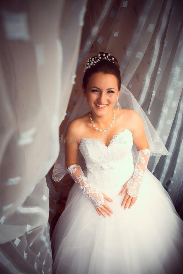 Gelukkige bruid die in venster kijken stock afbeeldingen