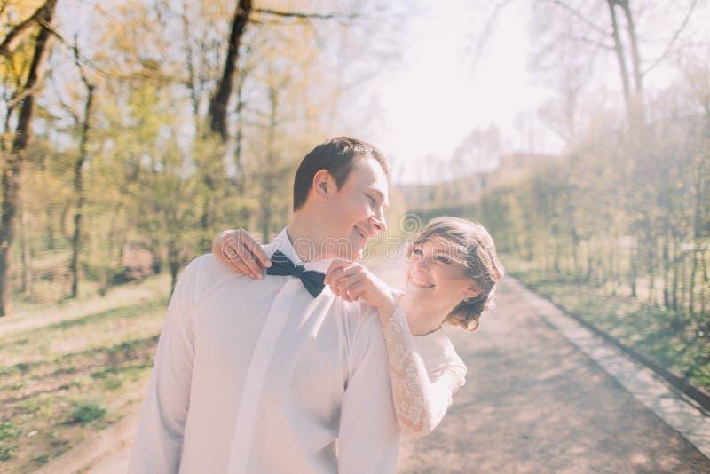 Gelukkige bruid die zich achter het bevestigen van blauwe vlinderdas van haar glimlachende bruidegom in wit overhemd bevinden stock foto