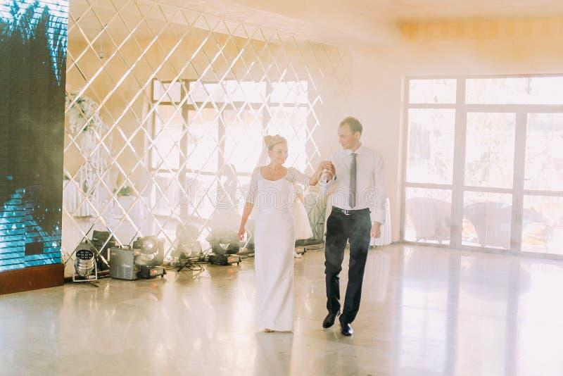 Gelukkige bruid en bruidegom bij hun eerste dans, huwelijk in het restaurant met een prachtige atmosfeer stock afbeelding