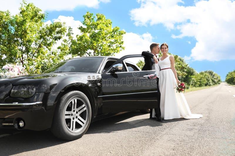 Gelukkige bruid en bruidegom dichtbij auto stock afbeelding