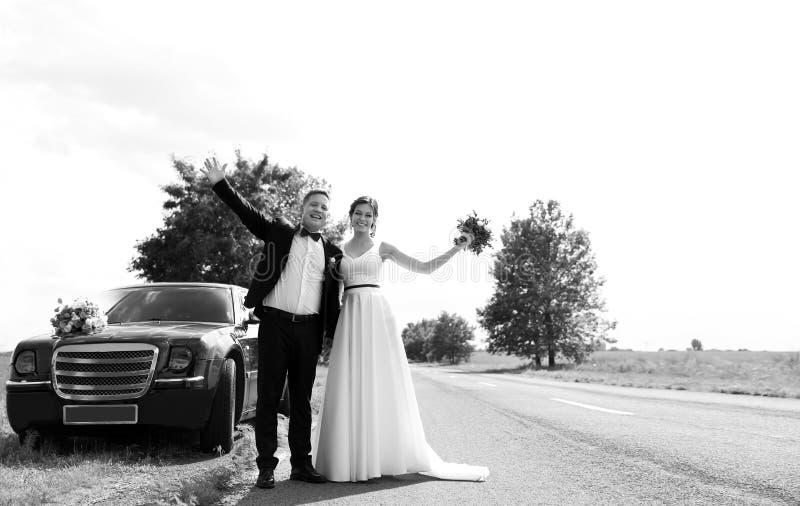 Gelukkige bruid en bruidegom dichtbij auto in openlucht stock foto