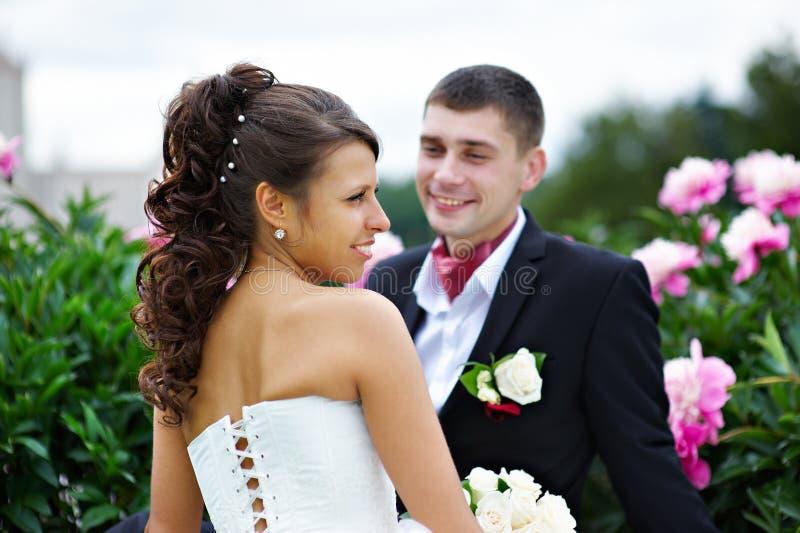 Gelukkige bruid en bruidegom dichtbij pioenbloemen royalty-vrije stock afbeeldingen