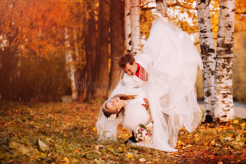 Gelukkige bruid en bruidegom die in de herfstpark dansen stock afbeeldingen