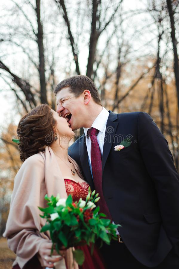 Gelukkige bruid en bruidegom die in het de herfstbos lopen stock afbeelding