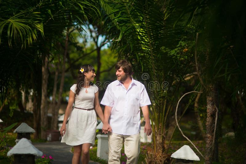 Gelukkige bruid en bruidegom die in het regenwoud lopen royalty-vrije stock foto