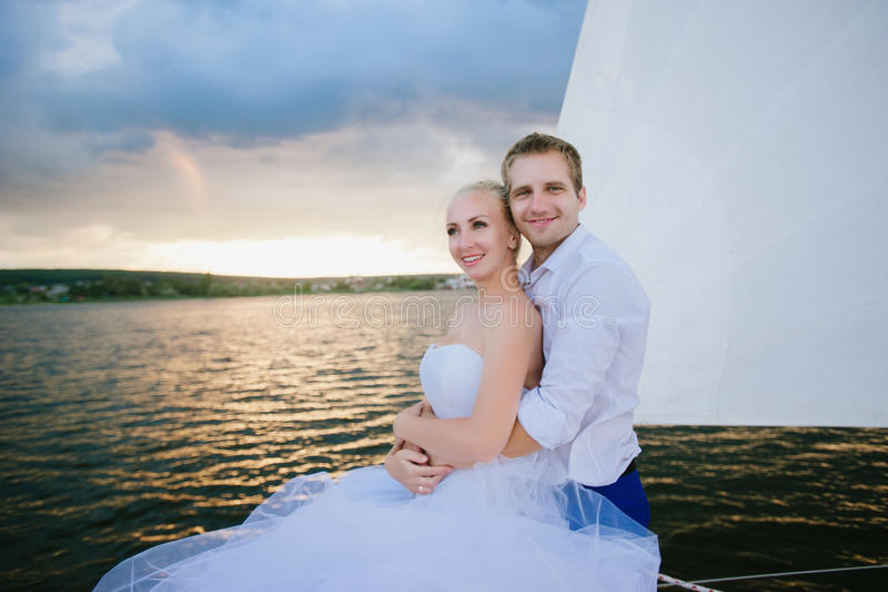 Gelukkige bruid en bruidegom die op een jacht koesteren royalty-vrije stock foto's