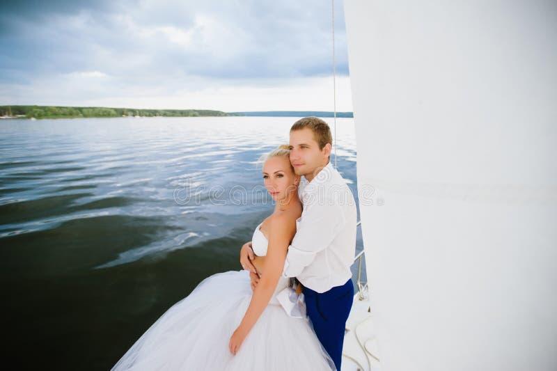 Gelukkige bruid en bruidegom die op een jacht koesteren royalty-vrije stock afbeeldingen