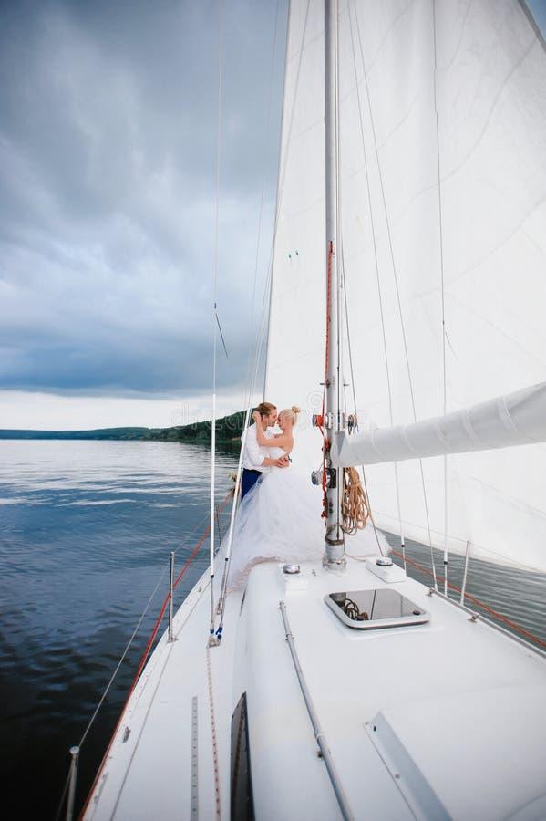 Gelukkige bruid en bruidegom die op een jacht koesteren royalty-vrije stock fotografie