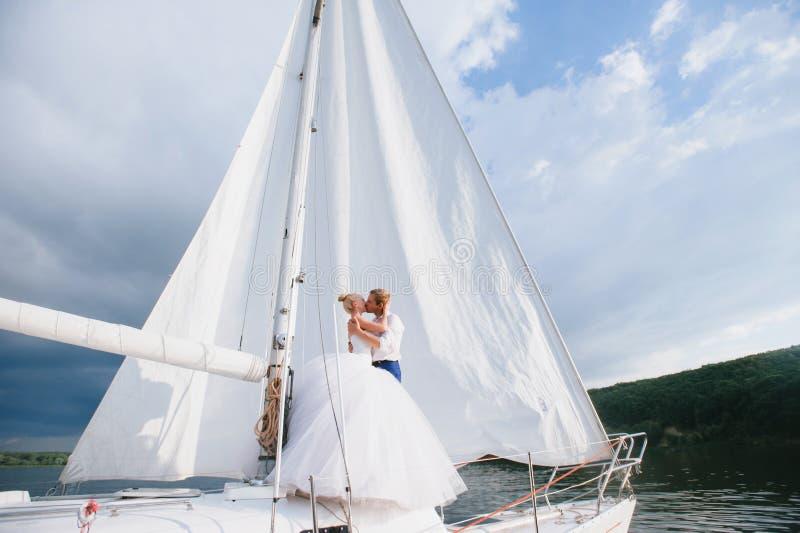 Gelukkige bruid en bruidegom die op een jacht koesteren royalty-vrije stock foto
