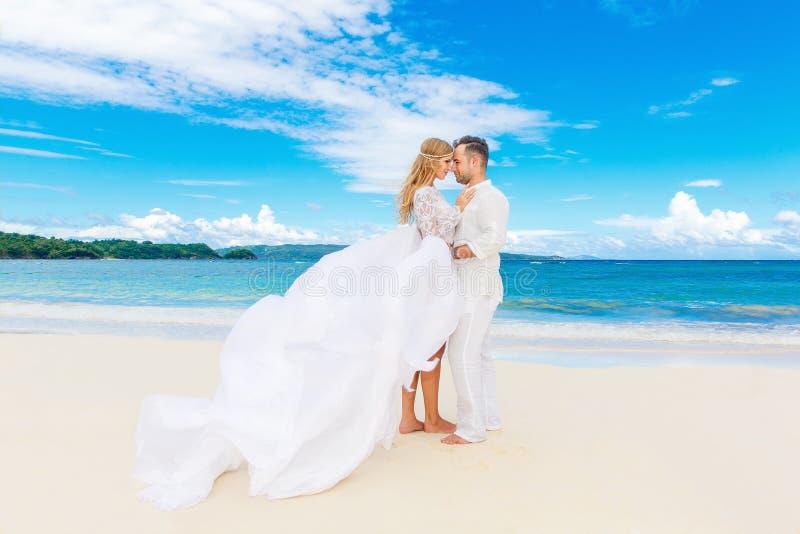 Gelukkige bruid en bruidegom die pret op een tropisch strand hebben Huwelijk stock foto's