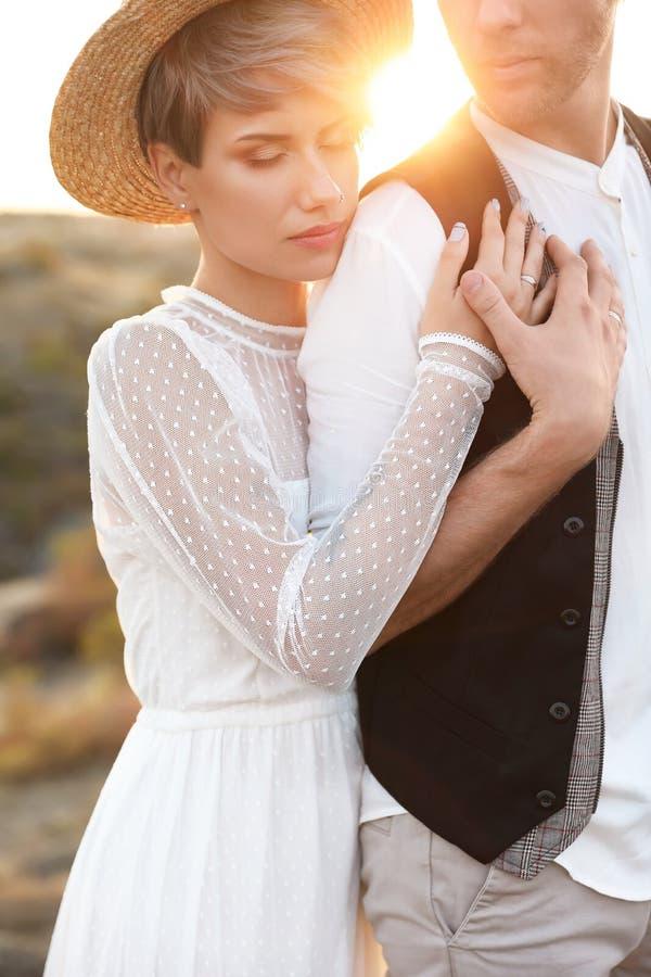 Gelukkige bruid en bruidegom die zich in openlucht bij zonsondergang bevinden royalty-vrije stock afbeeldingen