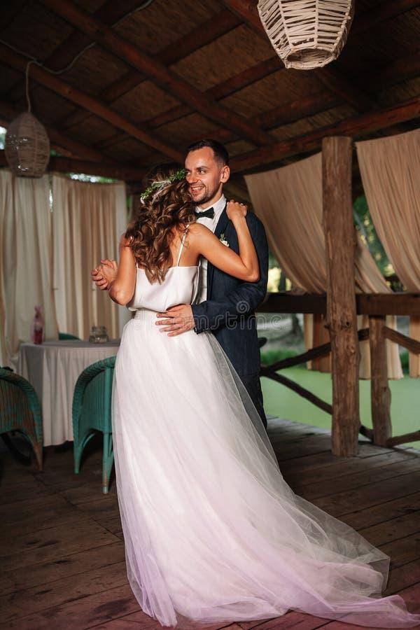 Gelukkige bruid en bruidegom en hun eerste dans, huwelijk in het elegante restaurant met een prachtig licht en atmosfeer stock afbeeldingen