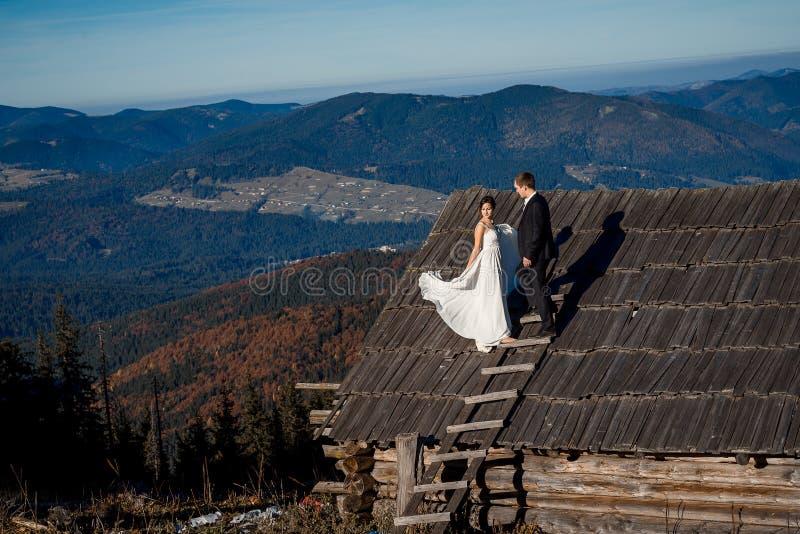 Gelukkige bruid en bruidegom op het dak van buitenhuis De adembenemende achtergrond van het berglandschap stock fotografie