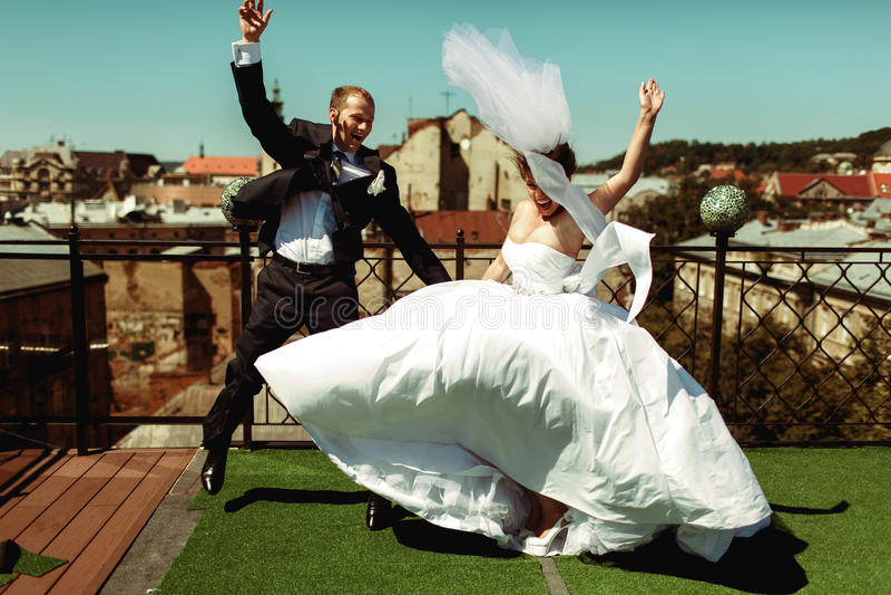 Gelukkige bruid en bruidegomsprong omhoog op het dak stock fotografie
