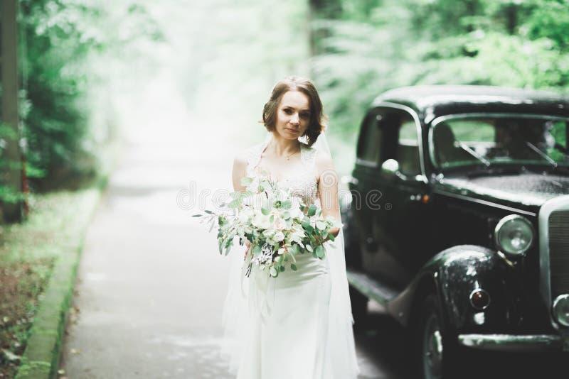 Gelukkige bruid in het retro auto stellen op haar die dag wieden stock foto's