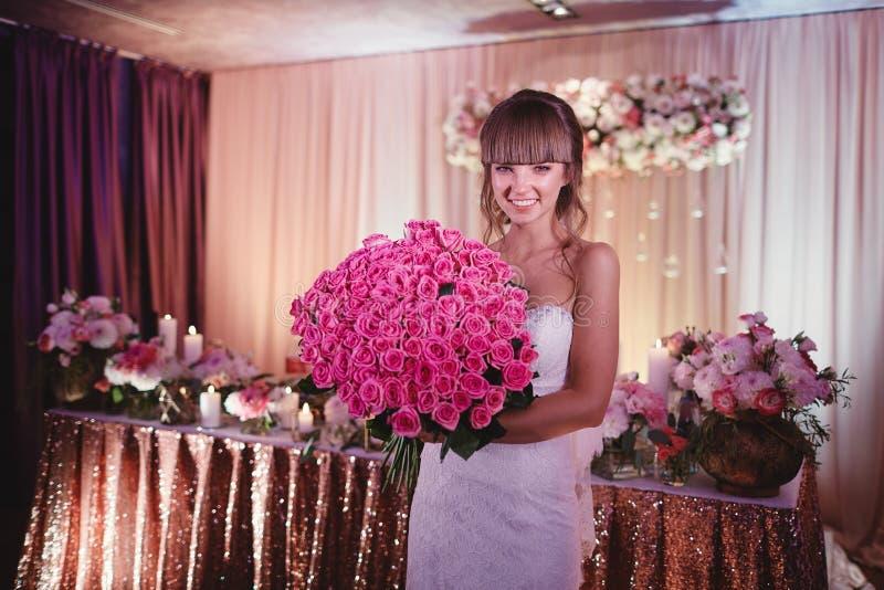 Gelukkige bruid met een groot boeket van rozen de mooie jonge glimlachende bruid houdt groot huwelijksboeket met roze rozen royalty-vrije stock afbeelding