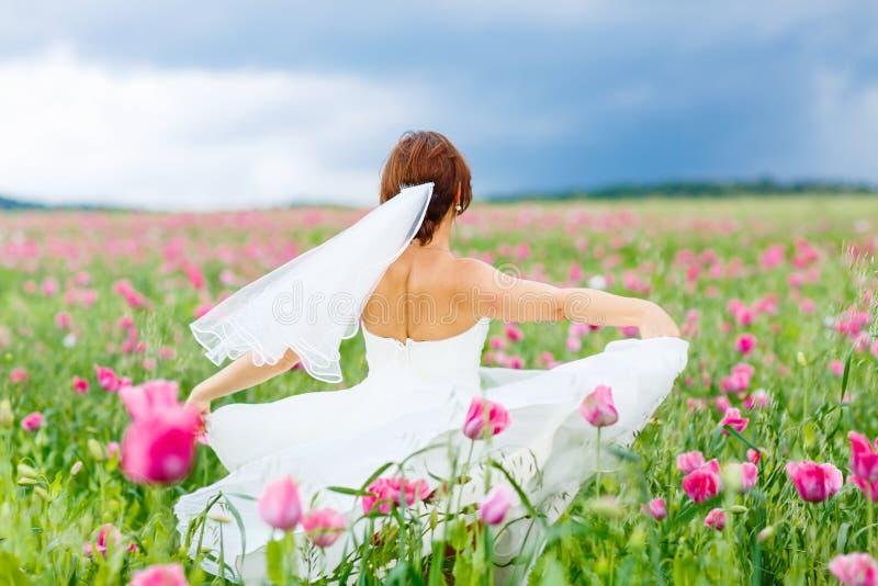 Gelukkige bruid in witte kleding die pret op het gebied van de bloempapaver hebben stock foto's