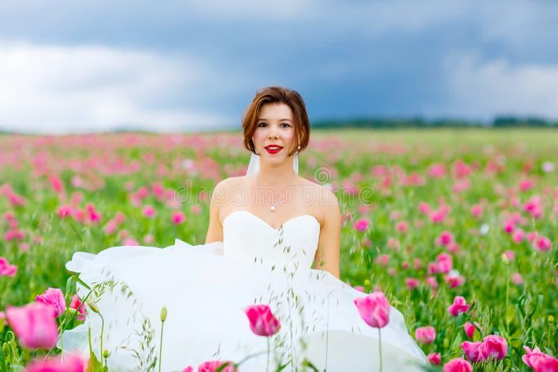 Gelukkige bruid in witte kleding die pret op het gebied van de bloempapaver hebben stock afbeelding