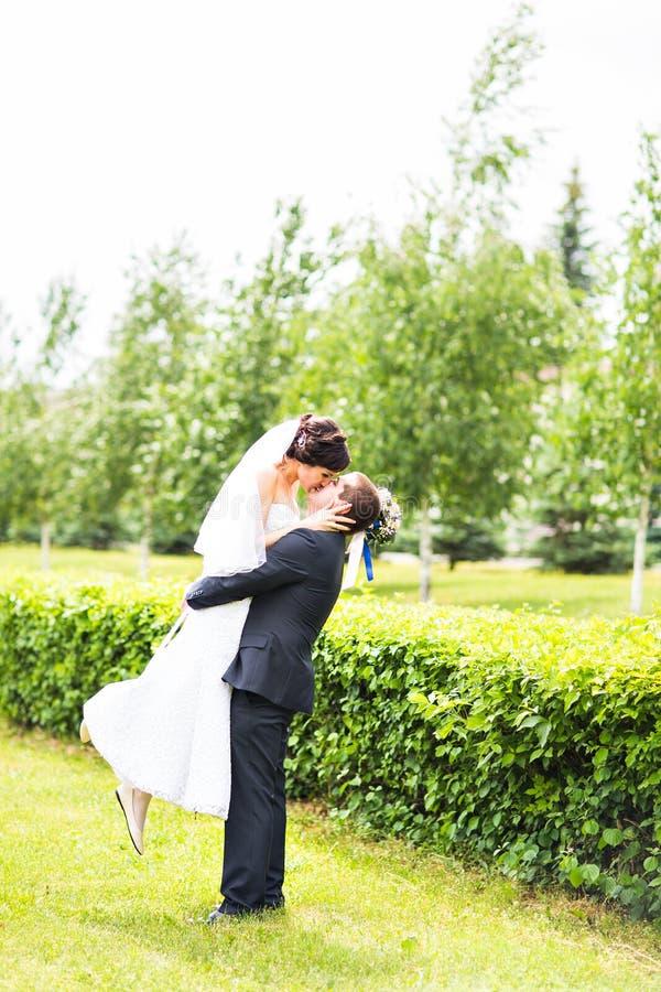 Gelukkige bruidegom die jonge mooie bruid in zijn wapens houden royalty-vrije stock foto