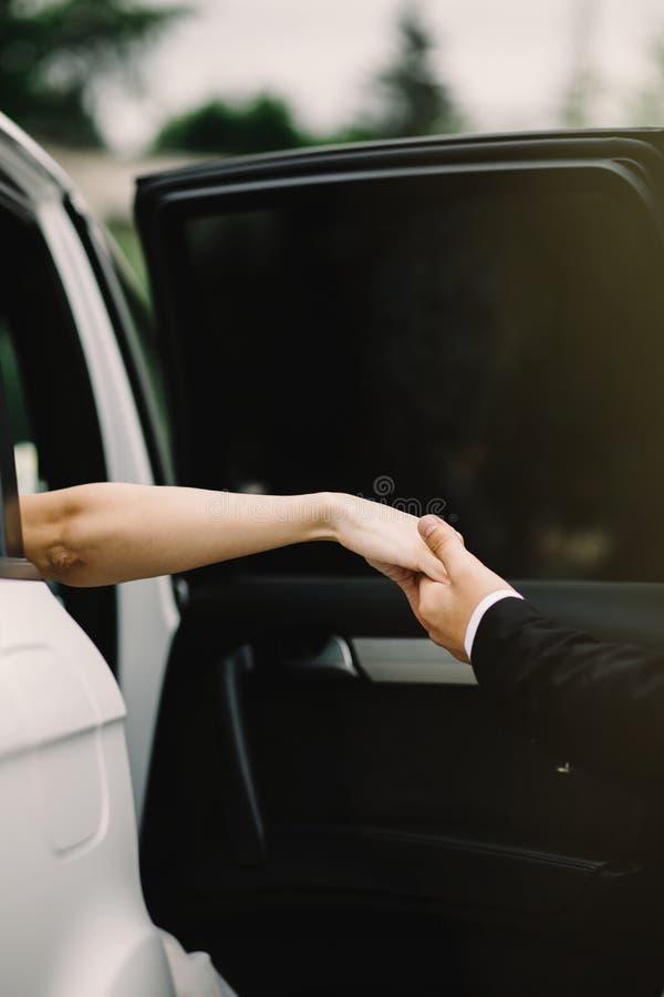 Gelukkige bruidegom die zijn mooie bruid helpen uit de huwelijksauto stock fotografie